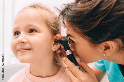 Photo Pediatrician examining little patient with otoscope, hearing exam of child