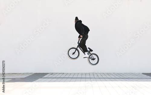 Young man in casual clothing makes a trick on a bmx bike. Bmx freestyle on the background of a white wall
