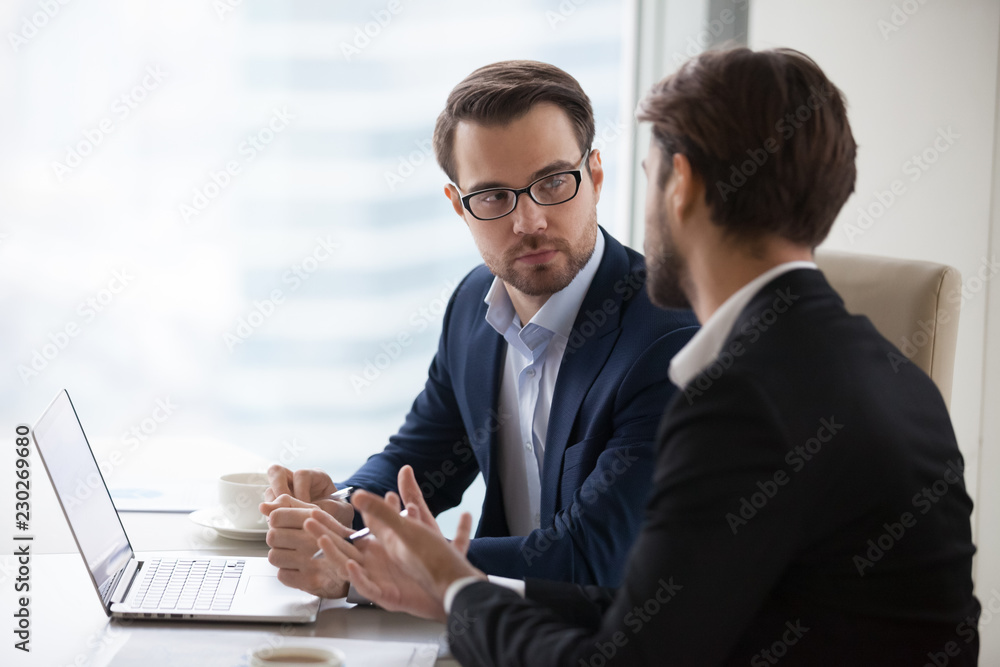 Fototapeta Two serious caucasian men in suits discussing or planning business issues in the office. Colleagues or client and consultant are sitting at the table next to each other and talking.