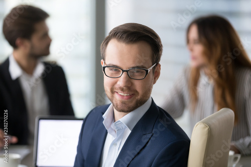 Obraz na płótnie Head shot portrait of confident businessman or business owner at workplace, smiling man sitting at briefing and looking at camera