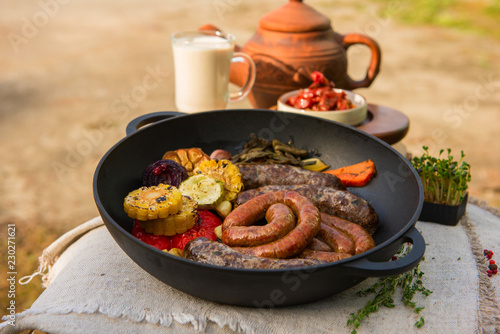 Grilled different meat sausages with vegetables and spices