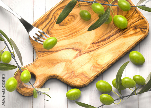 Olive branches on wooden rustic chopping board