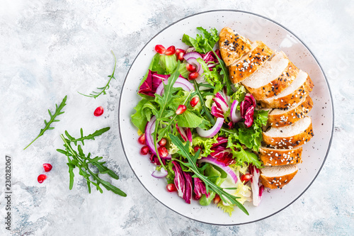 Canvas Prints Ready meals Grilled chicken breast, fillet and fresh vegetable leafy salad with arugula and pomegranate on plate