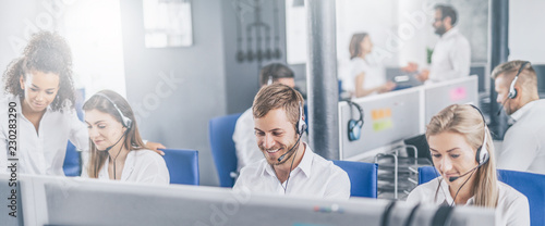 Call center worker accompanied by his team. Canvas Print