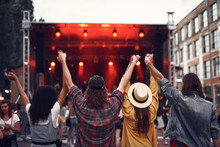 Back View Portrait Of Hipster Friends Holding Each Other Arms And Enjoying Performance Of Rock Band. Stage And Crowd On Blurred Background