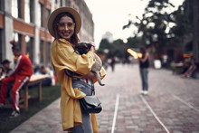 Portrait Of Stylish Hipster Girl In Hat Holding Cute Pug Puppy And Looking At Camera With Smile. Boulevard And People On Blurred Background