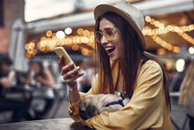 Side View Portrait Of Hipster Young Lady In Hat Reading Message With Good News On Mobile Phone. She Is Holding Little Pug Dog While Sitting At The Table