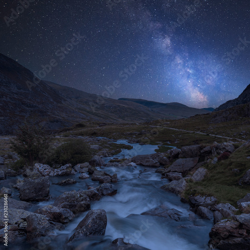Digital composite Milky Way image of Moody landscape image of river flowing down mountain range near Llyn Ogwen and Llyn Idwal in Snowdonia