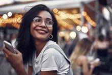 Portrait Of Hipster Young Lady In Glasses Holding Smartphone And Looking Away With Smile. Street With People On Blurred Background With Bokeh Effect
