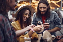 Our Four-legged Friend. Portrait Of Stylish Hipster Friends Looking At Cute Dog And Smiling. Bearded Guy Holding Beer