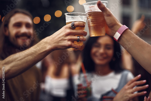 Cheers my friend. Close up of male hands clinking cups of cold beer