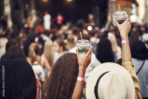 Spoed Foto op Canvas Cocktail Drink to that. Close up of female hands holding cups with mint beverage. Stage and crowd in blurred background