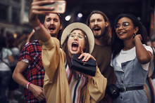 Waist Up Portrait Of Young Lady In Hat Taking Photo With Smartphone While Holding Purse. Group Of Hipsters Looking At Camera And Screaming With Joy