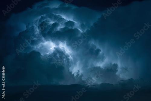 Fotografia Blue Lightning strike surrounded by storm clouds.