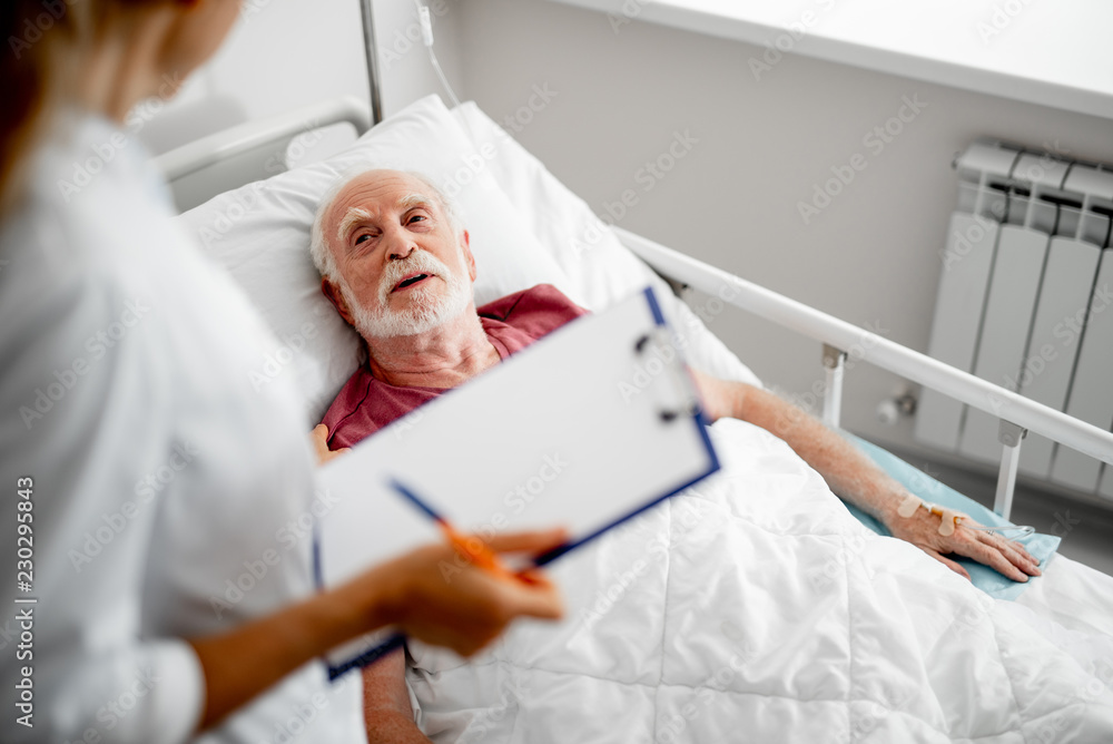 Fototapeta Thank you for your concern. Top view portrait of old man resting in hospital room and chatting with female therapist. Focus on bearded gentleman