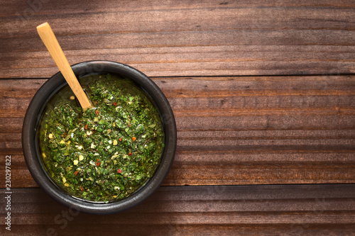 Raw homemade Argentinian green Chimichurri salsa or sauce made of parsley, garlic, oregano, hot pepper, olive oil, vinegar, photographed overhead with natural light (Selective Focus on the salsa)