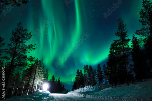 Wall Murals Northern lights Bright lamp shining on the empty snowy road just as the northern lights appear.