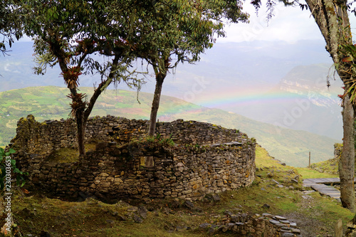 Fotobehang Zuid-Amerika land The trees growing inside rounded house ruins of Kuelap mountaintop citadel with the rainbow of lower hill in background, northern Peru