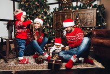 Portrait Of Happy Family Opening Christmas Gifts On The Carpet In Decorated Living Room.