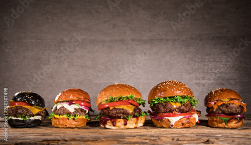 Tasty burgers on wooden table.
