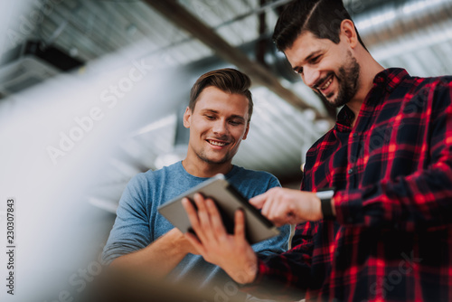 Delighted young male colleagues using tablet while working in the office