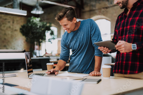 Cheerful enthusiastic young man using his laptop while brainstorming his business ideas with his friend