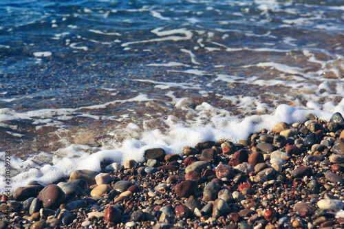 Waves washing over gravel beach, macro shot.