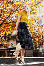 Outdoor Full Body Fashion Portrait Of Young Beautiful Smiling Girl Wearing Yellow Beret, Turtleneck, Polka Dot Midi Skirt, Ankle Boots, Wrist Watch, Holding Stylish White Bag, Posing In Autumn Street