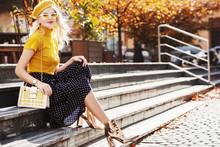 Outdoor Full Body Autumn Fashion Portrait Of Young Fashionable Girl Wearing Yellow Beret, Glasses, Turtleneck, Polka Dot Skirt, Ankle Boots, Holding Stylish White Bag, Posing In Street. Copy Space