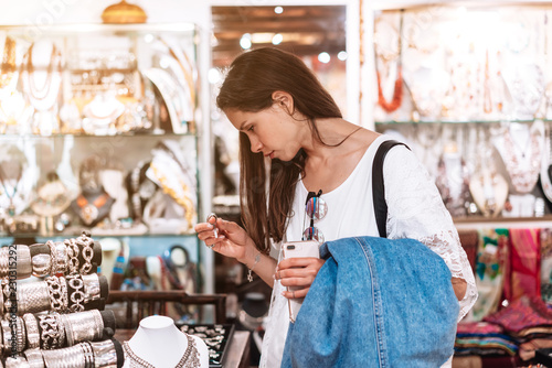 Photo girl chooses jewelry in a jewelry store.