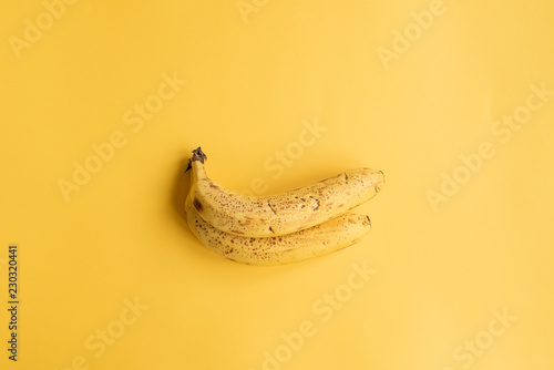 Valokuva  Two ripe smoothie bananas on yellow background from above