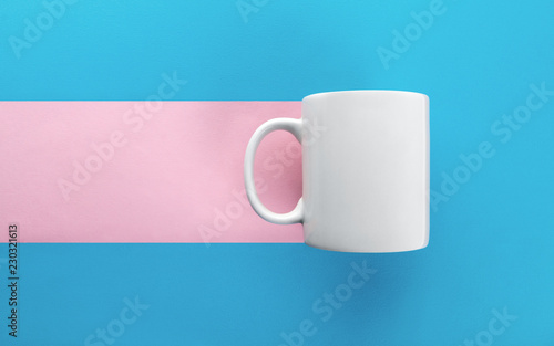 White mug on blue and pink background
