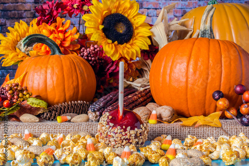 popcorn peanuts candy corn and red candy apple on blue table with background of fall flowers berries nuts autumn leaves yellow sunflowers and orange pumpkins on burlap