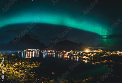 Foto auf Gartenposter Nordlicht Northern Lights Aurora Borealis with classic view of the fisherman s village of Reine near Hamnoy in Norway, Lofoten islands. This shot is powered by a wonderful Northern Lights show.