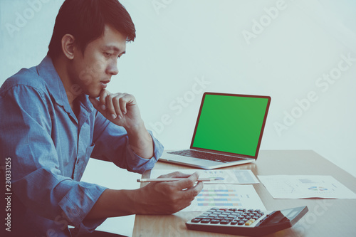 Fotografia  Middle aged thinking businessman working on green screen laptop and checking the