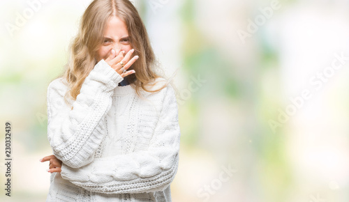 Fotografie, Tablou  Beautiful young blonde woman wearing winter sweater over isolated background smelling something stinky and disgusting, intolerable smell, holding breath with fingers on nose