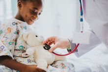 Doctor Playfully Checking The Heart Beat Of A Teddy Bear
