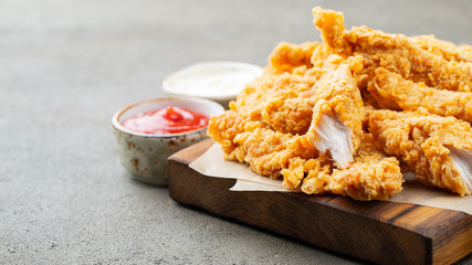 Breaded chicken strips with two kinds of sauces and fried potatoes on a wooden Board. Fast food on dark brown background. with copy space