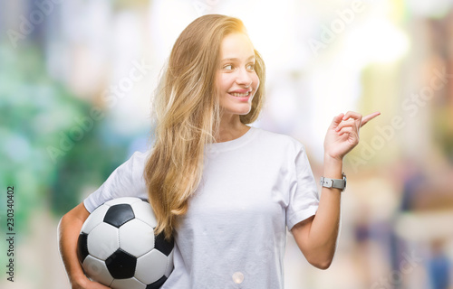 Cadres-photo bureau Jogging Young beautiful blonde woman holding soccer ball over isolated background very happy pointing with hand and finger to the side