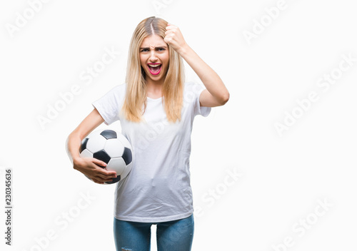 4d56885f1 Young beautiful blonde woman holding soccer ball over isolated background  annoyed and frustrated shouting with anger