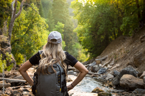 Vászonkép View from behind of a Woman hiking near a mountain stream while on vacation