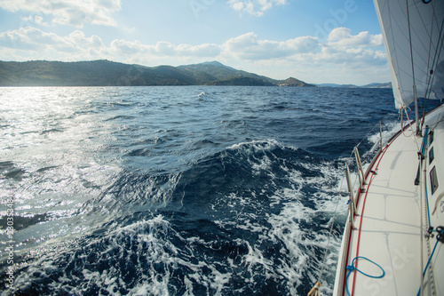 Sailing yacht glides on the sea, the waves come from under the boat.