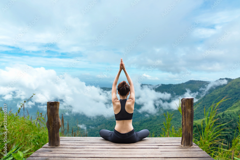 Fototapeta Healthy woman lifestyle balanced practicing meditate and zen energy yoga on the bridge in morning the mountain nature. Healthy life Concept.