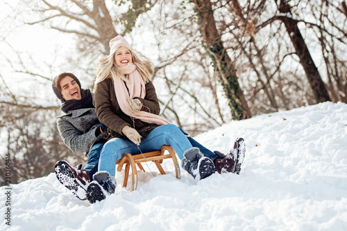 Obraz Two young people sliding on a sled  - fototapety do salonu
