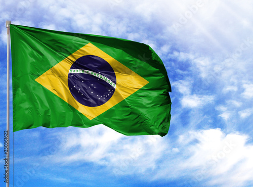 Foto  National flag of Brazil on a flagpole in front of blue sky