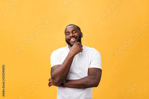 Fotografía  Portrait of a modern young black man smiling with arms crossed on isolated yello