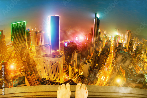 Fototapeten New York Barefoot Hong Kong girl on a skyscraper roof jumping for suicide, over Tokyo cityscape at night. High Japan skyscraper with city lights of Wan Chai district. Depression and stress urban life concept.
