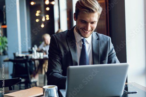 Fotografía Attractive businessman using a laptop and smiling while working in cafe