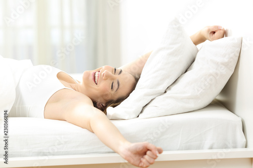 Happy woman waking up stretching arms at home