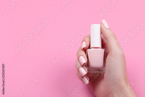 Fotografie, Obraz  girl holds nail polish with a beautiful manicure